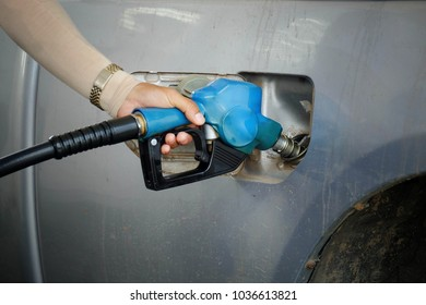 close up worker hand holding blue nozzle fuel for fill oil into car tank at pump gas station, saving money and energy for transport, transportation technology, manage for success business