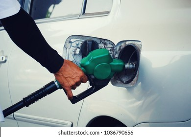 close up worker hand holding green nozzle fuel to fill oil into car tank at pump gas station, saving money and energy for transport, transportation technology, manage for success business concept