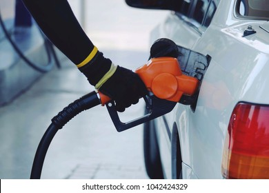 close up worker hand holding orange nozzle fuel for fill oil into car tank at pump gas station, saving money and energy for transport, transportation technology, manage for success business concept