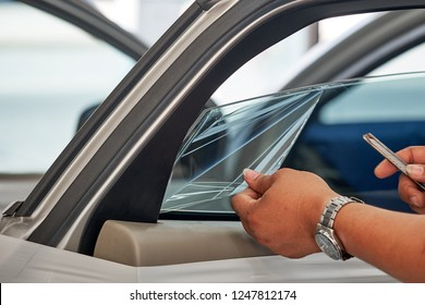 Close up of worker hand removing car window tint on side window. Professional gently lift corner of the film using razor blade and carefully grab the corner and peel it from the surface of glass.