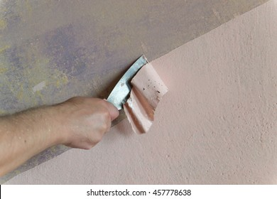 Close up worker hand scraping old paint on concrete wall. Remover old paint. Manual work with scraper. preparation for painting a room
