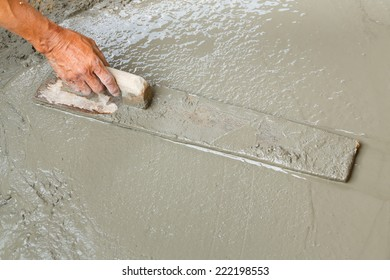 Close up worker hand using float to level surface of concrete