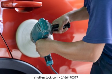 Close up of worker hands using an auto polisher to polish the car body in garage. Auto service, Car Painting, Machine washing Concept.
