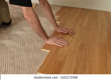 close up of worker installing wood parquet