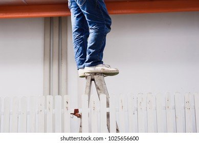 Close up worker legs standing on the ladder at construction site.Risk management concept.