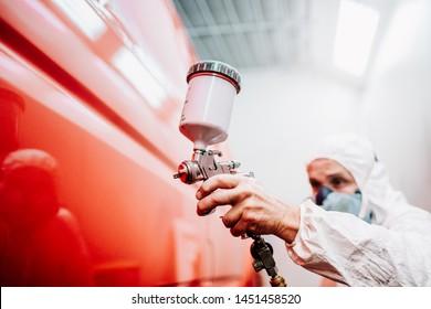 Nahaufnahme eines Arbeitnehmers, der ein rotes Auto in einer speziellen Garage mit weißer Tracht anstrich