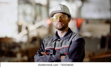 Close up of working man in uniform dressed in protective hardhat and eyeglasses standing in construction area and looking at the camera.
