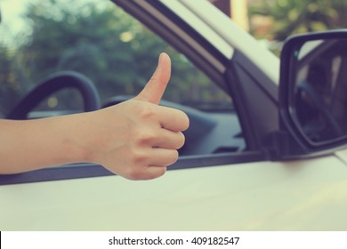 close up working woman hand show thumb up through car's window for safety and assurance of driving concept