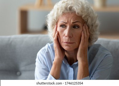 Close up worried elderly 70s woman seated on sofa touch head with hands deep in sad thoughts, memory loss dementia mental problems, chronic senile diseases symptoms, life troubles, loneliness concept