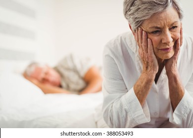 Close up of worried senior woman sitting on bed in bedroom