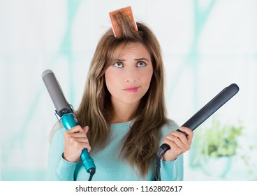 Close up of a worried woman using a hair roller in ther head and holding two straighteners in both hands in a blurred background