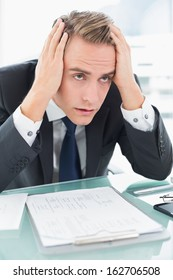 Close up of a worried young businessman sitting at office desk