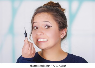 Close up of worried young woman holding a eyeliner and doing crazy make-up in her face, in a blurred background