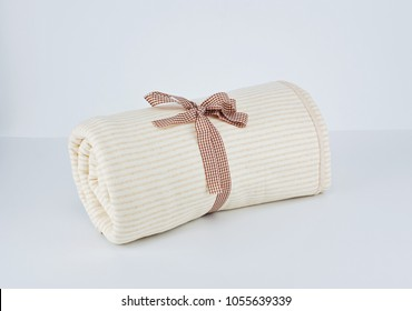 Close up wrapped natural beige cotton blanket for kid on white background with ribbon. Sensitive skin care concept