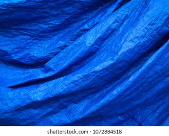 Close up of a wrinkled blue tarp.