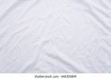 Close up of wrinkled white color fabric bed sheet texture background.