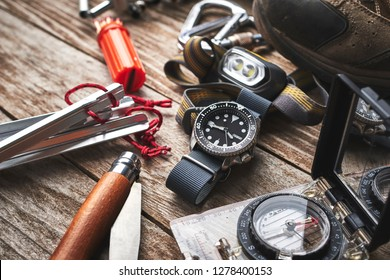 close up of wrist watch, compass, knife and other camping gear