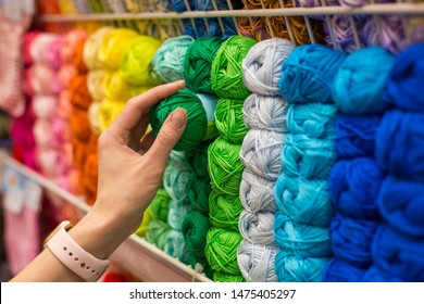 Close Up of yarn balls. Girl hand choosing Yarn in Knitting Shop. knitting shop center. A lot of color yarn for knitting. Selection of colorful yarn wool on shopfront