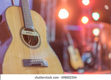 Close up yellow acoustic guitar on a stand in front of a stage set up for an upcoming concert.
