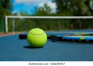 Close up of yellow ball is on tennis racket background, laying on blue tennis court carpet. Photo of professional sport equipment. Concept of tennis outfit photografing.