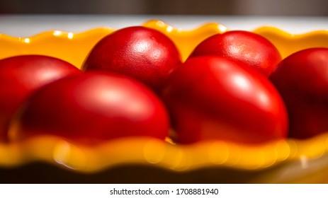 Gros plan sur un bol jaune avec des oeufs de Pâques rouges. Les oeufs peints en rouge sont le symbole des fêtes de Pâques.