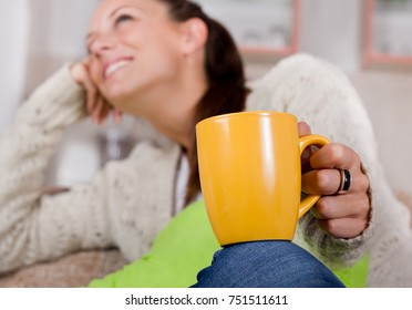 Close up of yellow cup of tea on girl's knee with happy smiling face blurred in background. Young woman sitting on sofa and relaxing in cozy warm home atmosphere