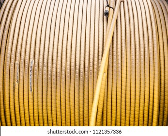 Close up yellow electric power cables wires in reel roll coil spool bobbin