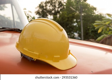 Close up of yellow engineer's helmet is placed on the hood of a truck.