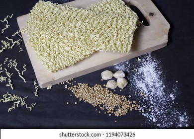 close up of yellow instant noodles with flour, candlenut, coriander,  dark background
