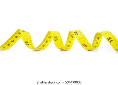 Close up of a yellow measure tape coiled, isolated on white background