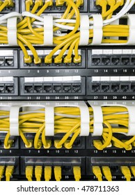 Close up of yellow network internet cables, patch cords connected to black switch, router in data center