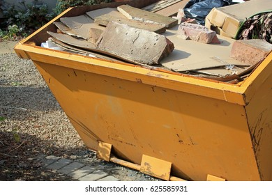 Close up of a yellow skip with rubbish and construction waste