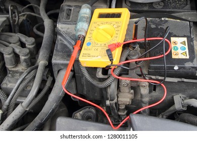 Close up yellow tester digital multimeter on old black car battery accumulator with electrolyte acid drips - repair of vehicle electrical equipment