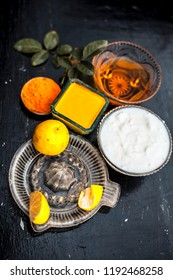 Close up of yogurt or curd face pack with honey,lemon juice,turmeric powder for acne skin on wooden surface in a glass container with raw lemon and turmeric powder.