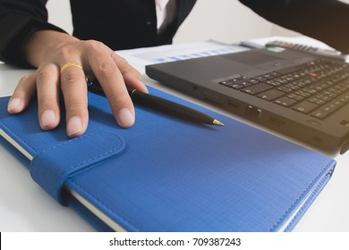 Close up yong hands placed on the notebook with open laptop. Get ready the working