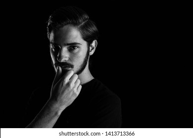 Close up of young adult male looking sinister or contemplative. Monotone, black and white for dramatic effect, dark and moody series. Concept image for corporate scheming. Thumb rubbing lips.