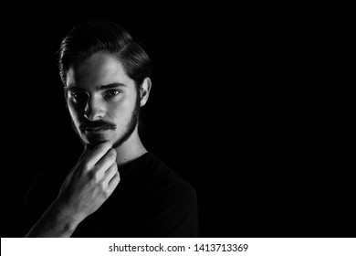 Close up of young adult male looking sinister or contemplative. Monotone, black and white for dramatic effect, dark and moody series. Concept image for corporate scheming. Hand on chin in thinking.