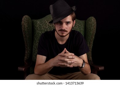 Close up of young adult male looking sinister or contemplative. Color dark tones for dramatic effect, dark and moody series. Concept image for magician in wingback chair unhappy and scheming.