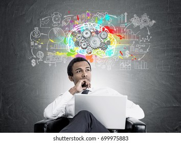 Close up of a young African American businessman sitting in a large black armchair with a laptop and looking to the distance. Blackboard with a colorful brain sketch, gears and a business plan
