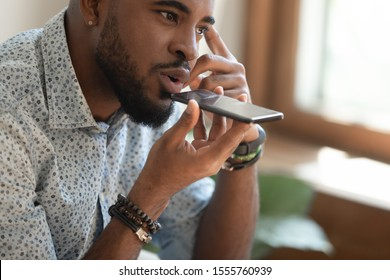 Close up of young african American man hold cellphone talk using virtual digital voice assistant, siri activation, biracial male speak on speakerphone loudspeaker on smartphone, record audio message