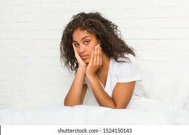 Close up of a young african american tired woman sitting on the bed