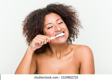 Close up of a young african american woman brushing her teeth with a toothbrush