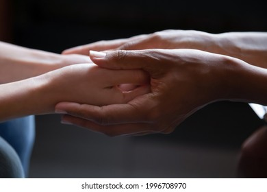 Close up young african american woman holding hand of female caucasian friend, giving psychological help, supporting in difficult life situation. Sincere mixed race people holding trusted conversation