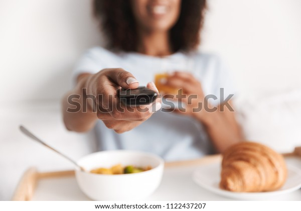 Close up of young african woman holding tv remote while having tasty breakfast on a tray in bed