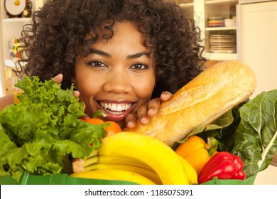 Close up of young African woman smiling with food produce in grocery bag