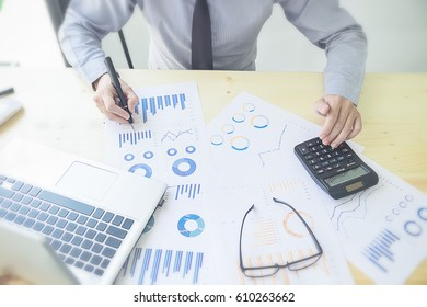 Close up young Asian Business man using a calculator to calculate the numbers. discussion and analysis data the charts and graphs showing the results.Business finances and accounting concept Business