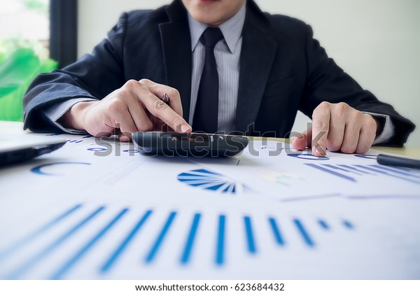 Close up young Asian Business man using a calculator to calculate the numbers.Business finances and accounting concept