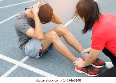Close up of young asian couple doing sit-ups on the blue running track in stadium