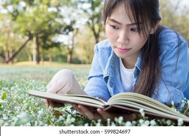 Close up young asian girl lying on flower field and reading books on clear day