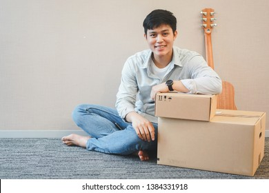 close up young asian man sitting with box and guitar prepare for decor in new residence , millennial and house concept
